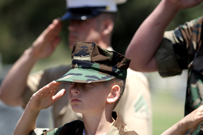 Cpl. Adams and members of the MCAS Miramar Young Marines chapter salute the colors during a Memorial Day event.