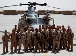 "Cpl. Brandon Moore, an infantryman with 1st Battalion, 8th Marines, (back row right, in front of helicopter door) poses with his squad and the Marine Light Attack Helicopter Squadron 469 ""Vengeance"" aircrew who provided vital close air support during the ill-fated June 22, 2012, Operation Jaws, on the Camp Bastion, Afghanistan, flightline in July 2012."